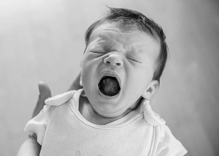 Mobiles Neugeborenenfotoshooting in Berlin | Babyfotos Zuhause Fotograf, baby gähnt